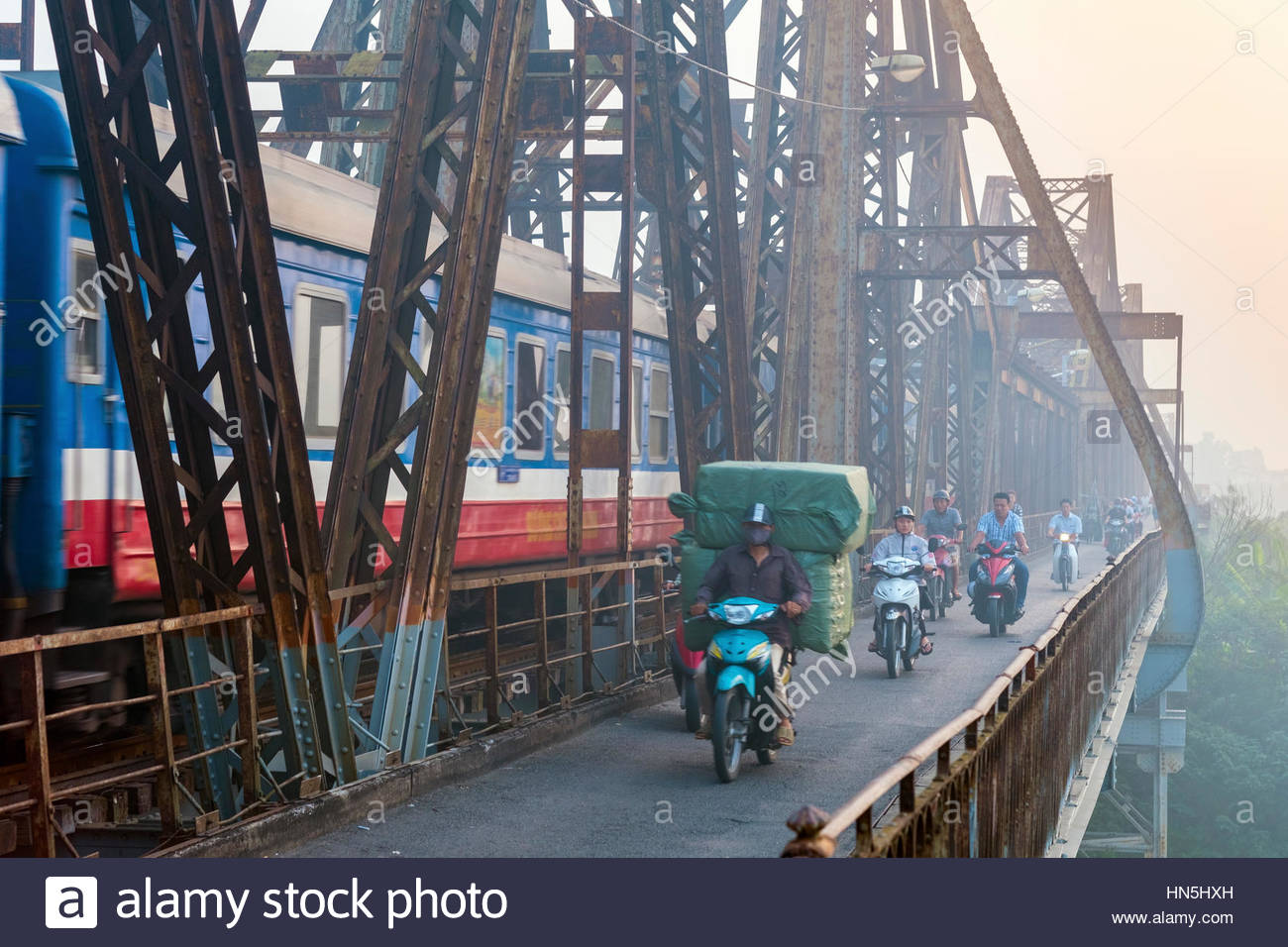 Heavy commuter motorbike traffic and a train on the Long Bien cantilever bridge, Hanoi, Vietnam - Stock Image