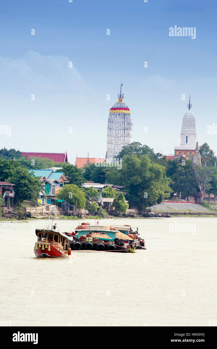 Barge on the Chao Phraya river in Ayutthaya with temple stupas behind - Stock Image