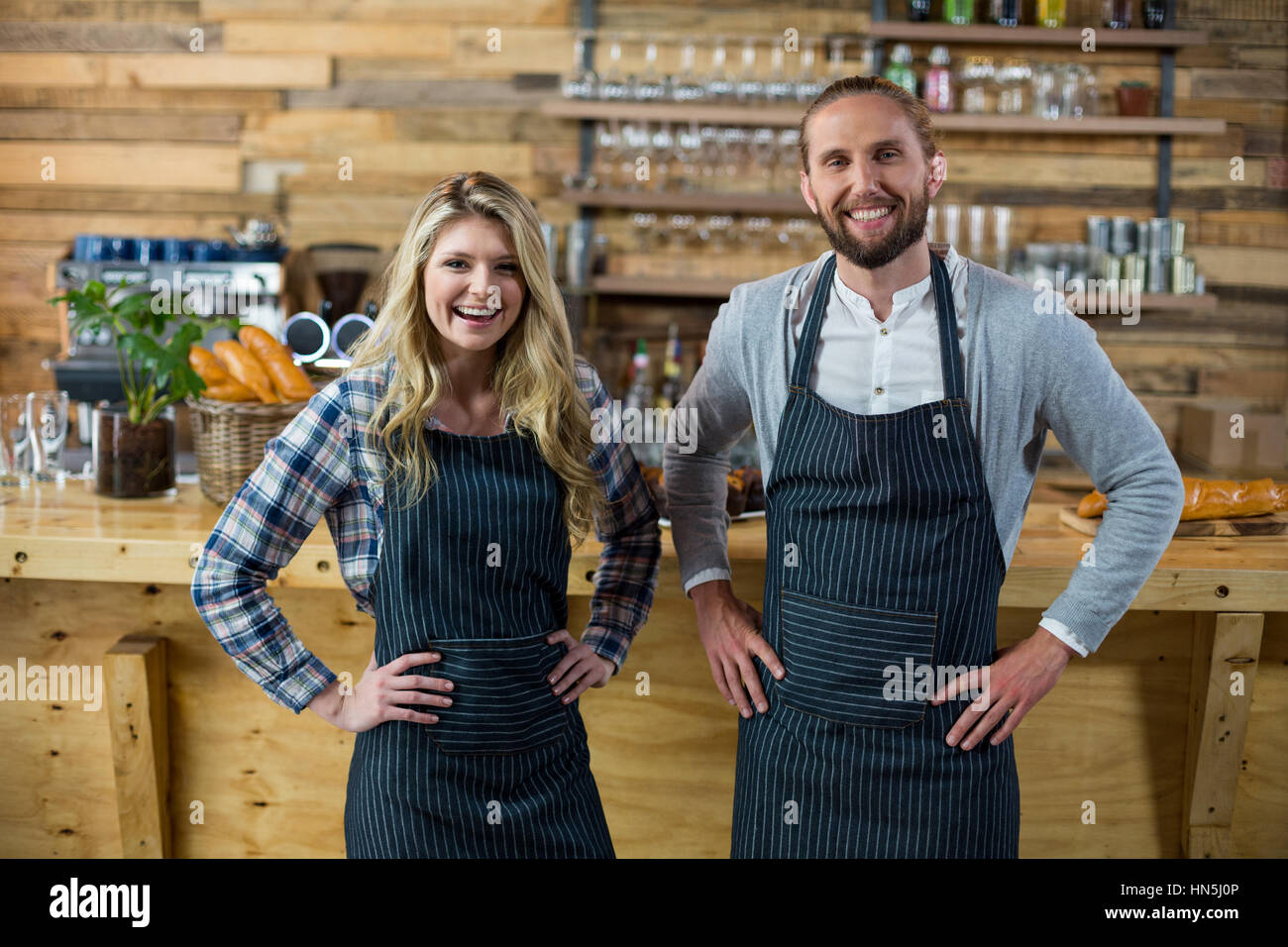 Portrait of waiter and waitress standing with hand on hip at counter in café - Stock Image
