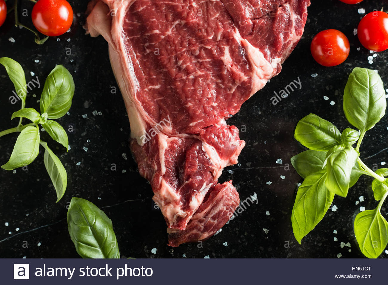 Fresh steak served with spices, tomatoes and leafs of basil on marble background. Uncooked beefsteak cooking on - Stock Image
