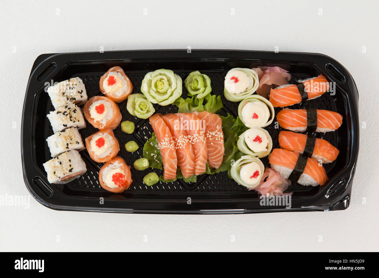 Assorted sushi set served in black box against white background - Stock Image