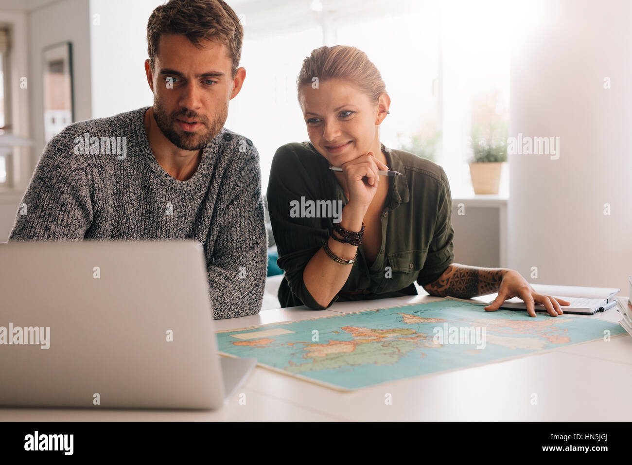 Young man and woman looking at laptop computer with world map in front. Couple using technology to explore the world. - Stock Image