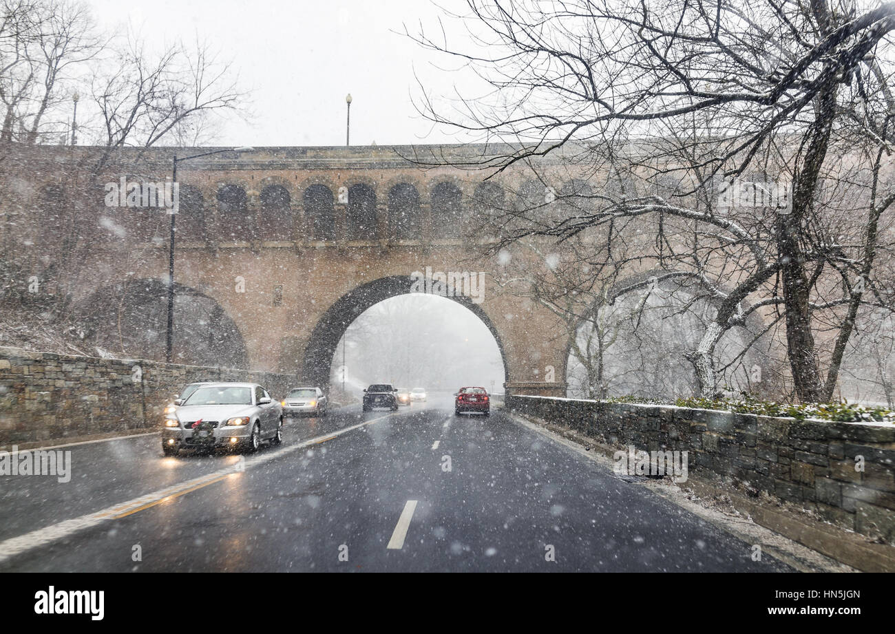 Washington DC, USA - January 7, 2017: Winter snow storm on road with cars and Dumbarton bridge with arches - Stock Image