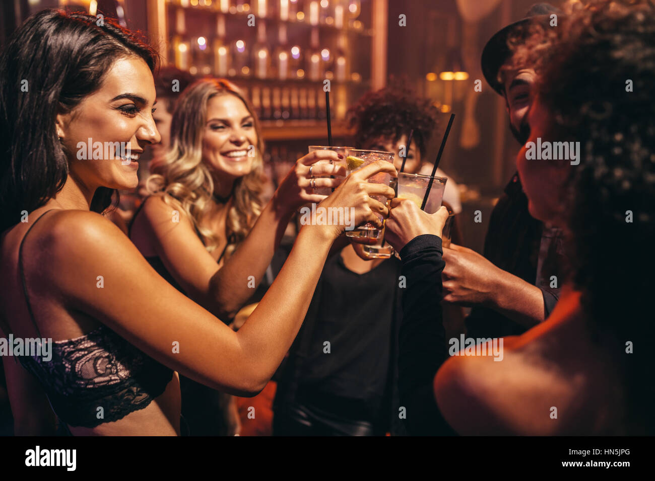 Group of young people with cocktails at nightclub. Best friends partying in a pub and toasting drinks. Stock Photo