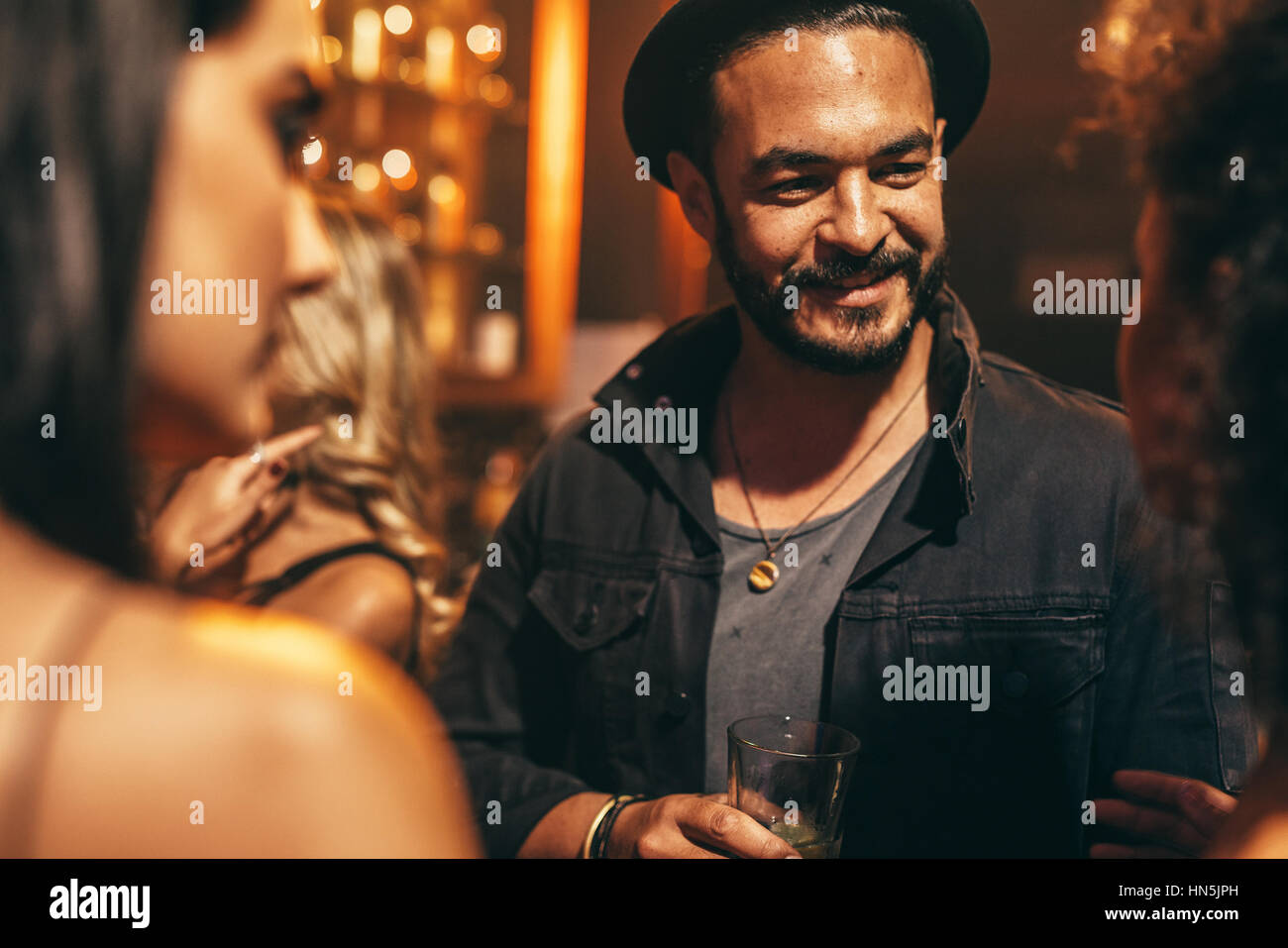 Handsome young man having party with friends at nightclub. Young people at pub having good time. - Stock Image