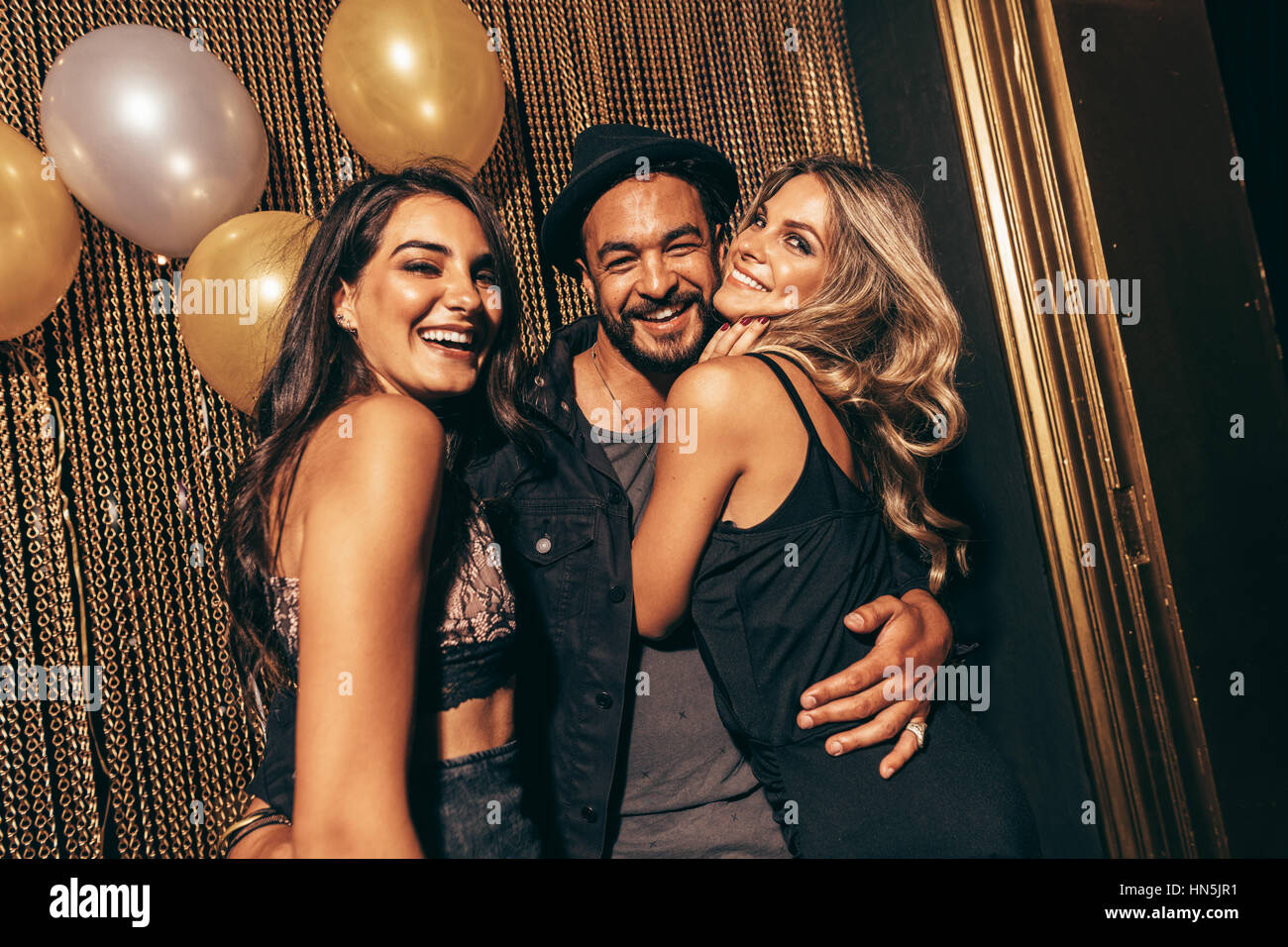 Portrait of handsome man with female friends at disco. Young friends in a party at nightclub. Stock Photo