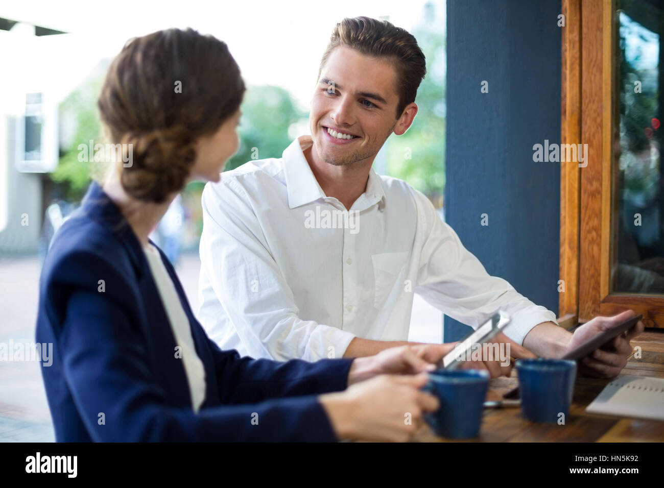 Businessman and woman interacting while having coffee at counter in café Stock Photo