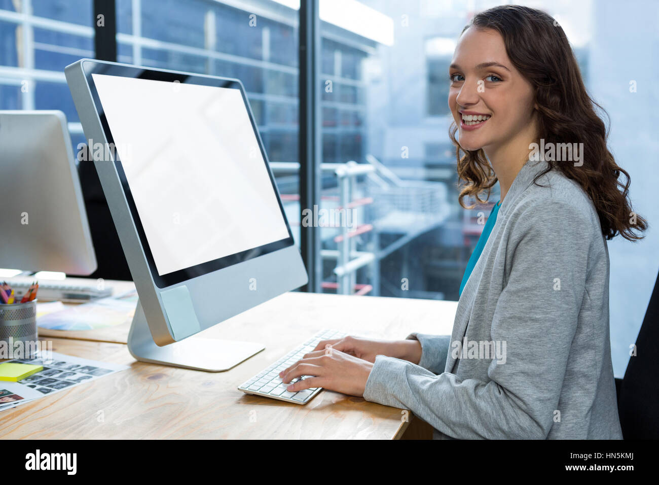 Portrait of female graphic designer working over computer at desk in office - Stock Image