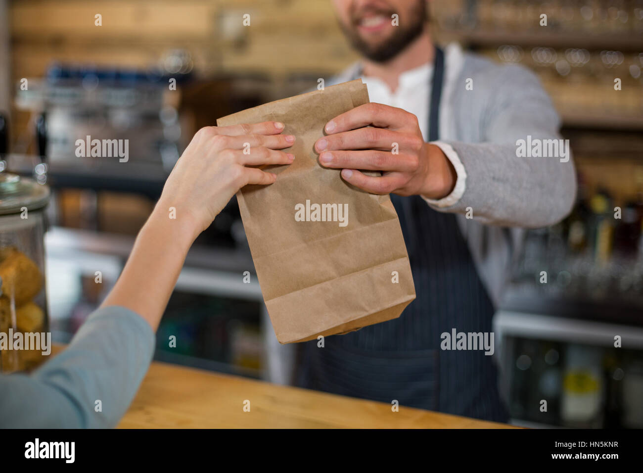Woman receiving parcel from waiter at counter in cafe - Stock Image