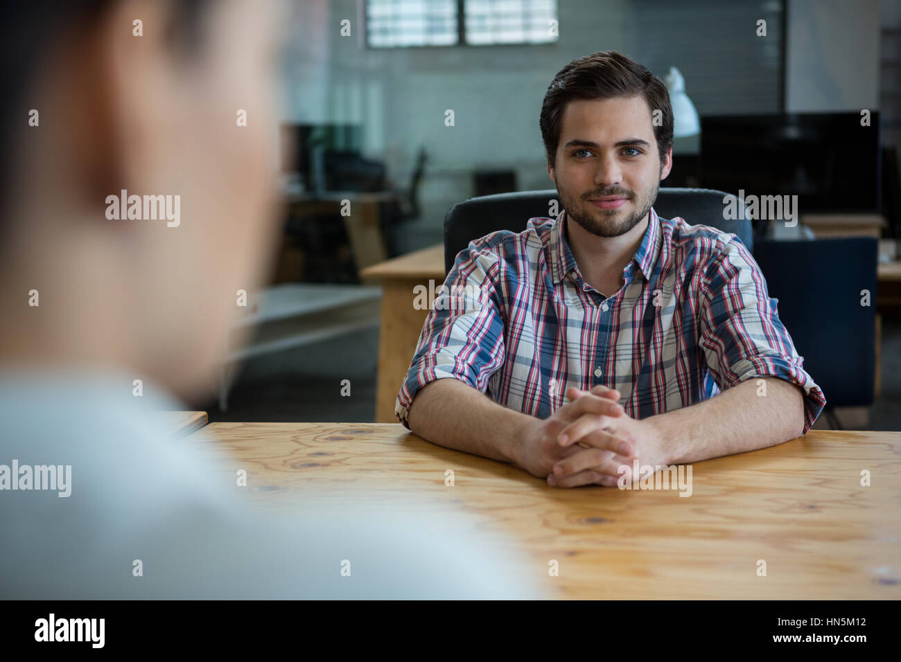 Business executive conducting job interview with woman in office - Stock Image