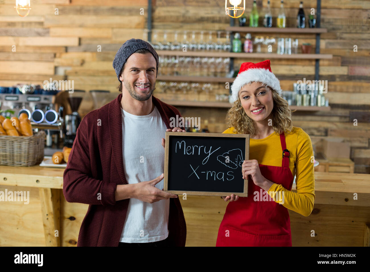 Portrait of smiling waitress and owner standing with merry x mas sign board in cafe - Stock Image