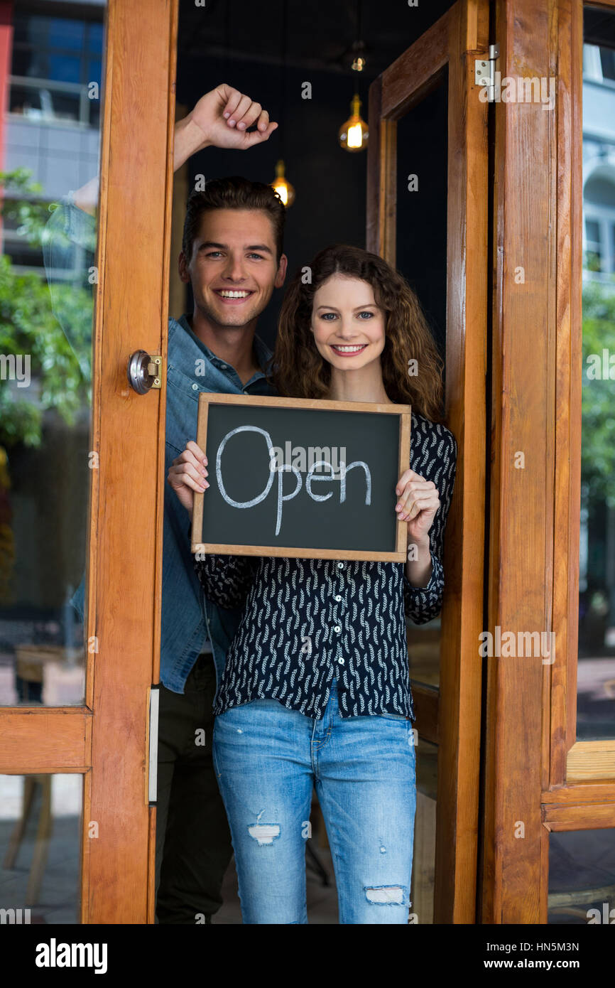 Portrait of man and woman showing chalkboard with open sign at café - Stock Image