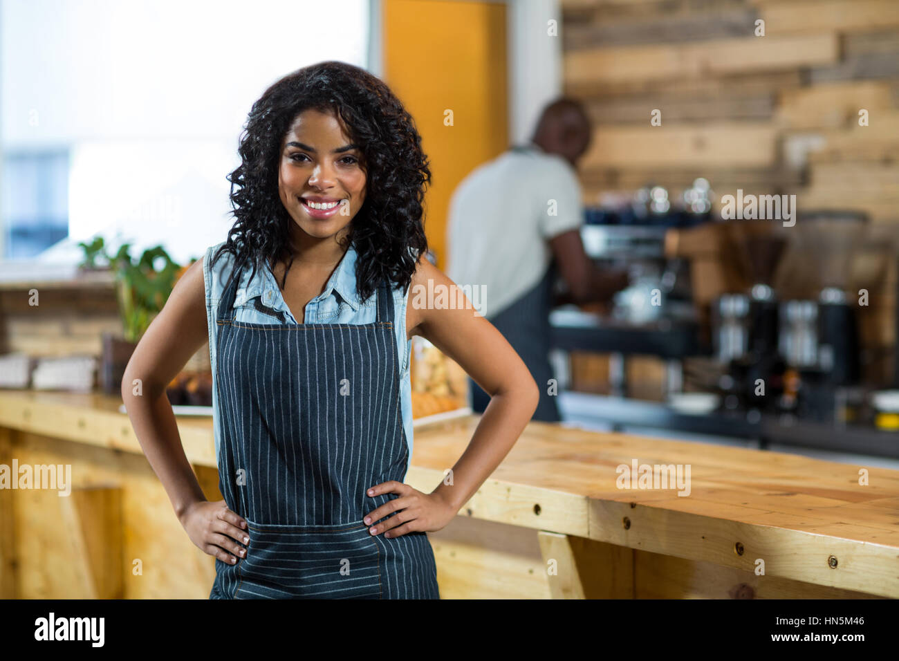 Portrait of smiling waitress standing with hands on hip at counter in café - Stock Image