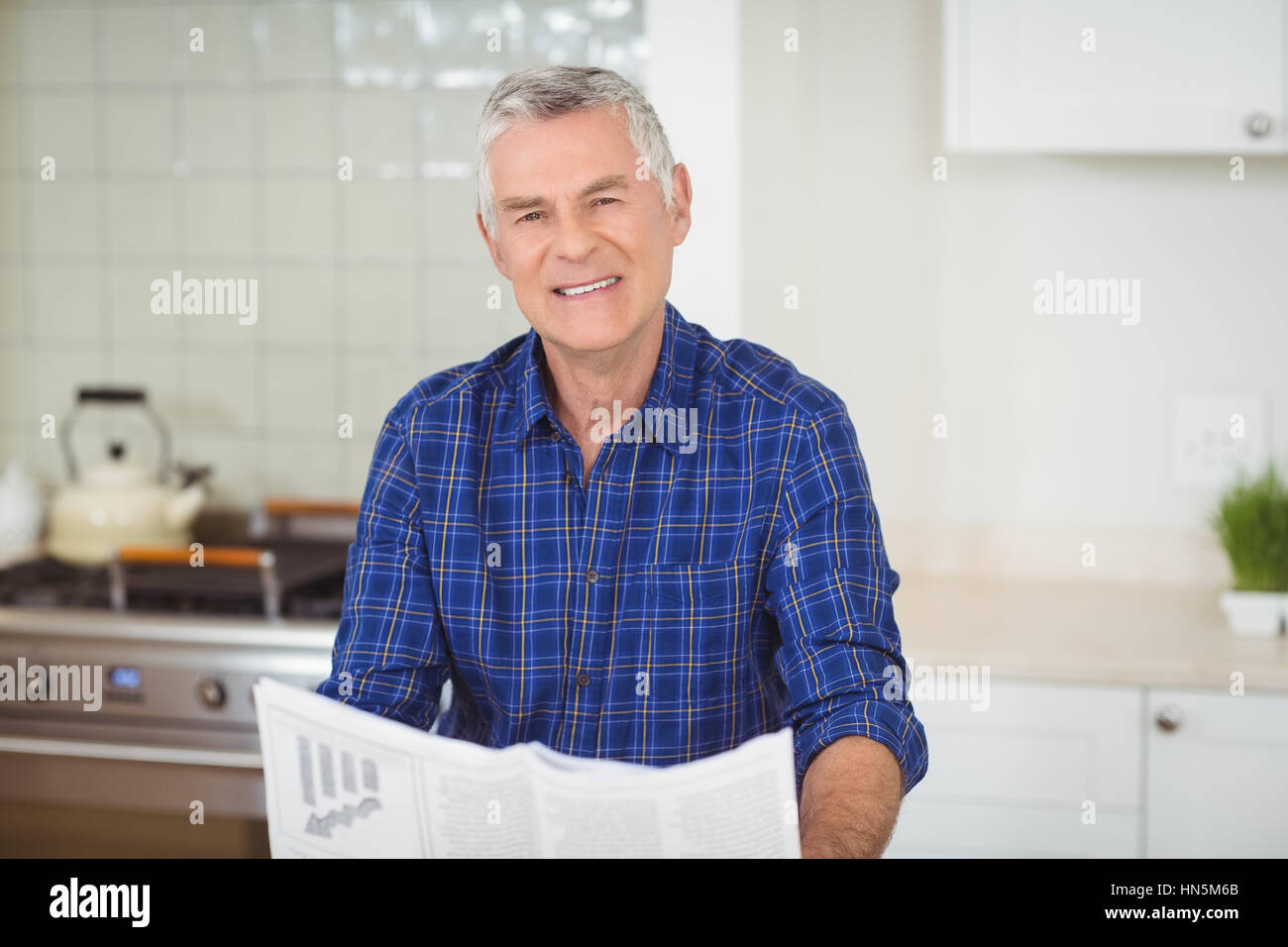 Portrait of senor man reading newspaper in kitchen at home - Stock Image