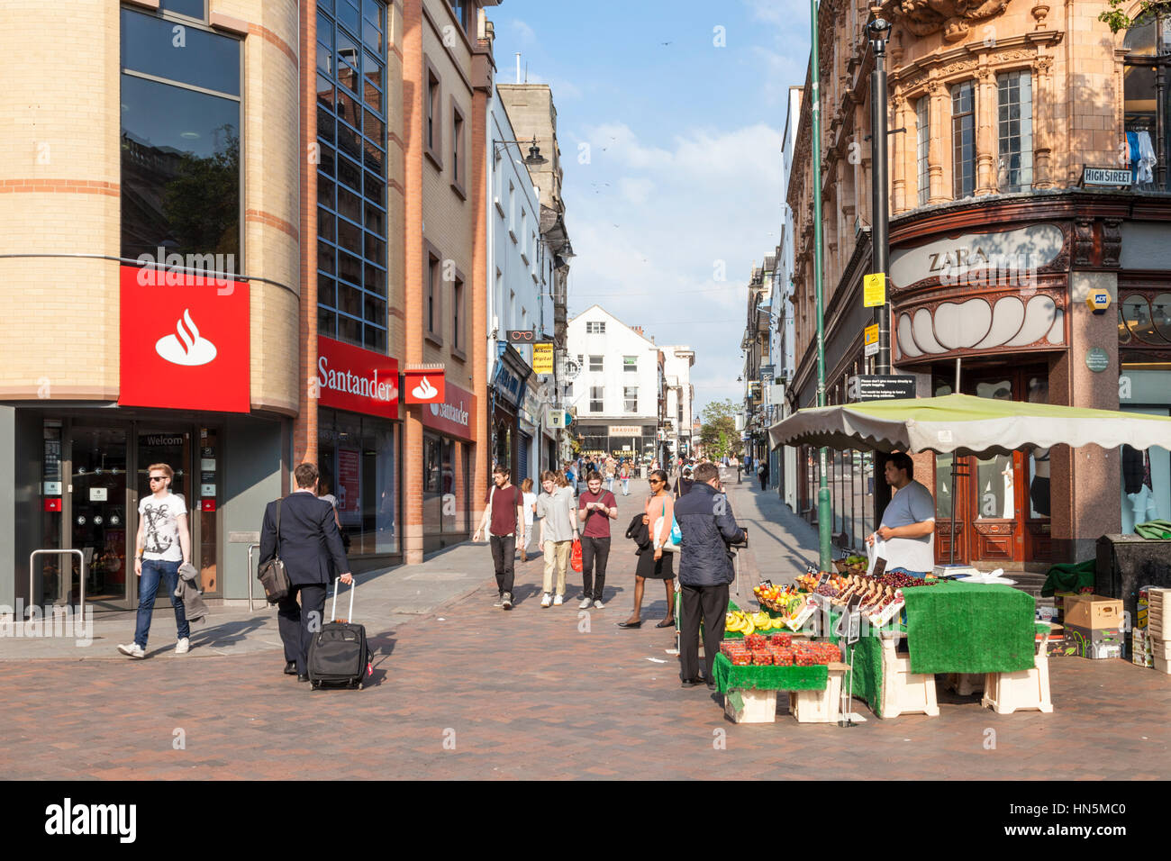 Market trader and other people in a street view of Nottingham city centre, England, UK - Stock Image