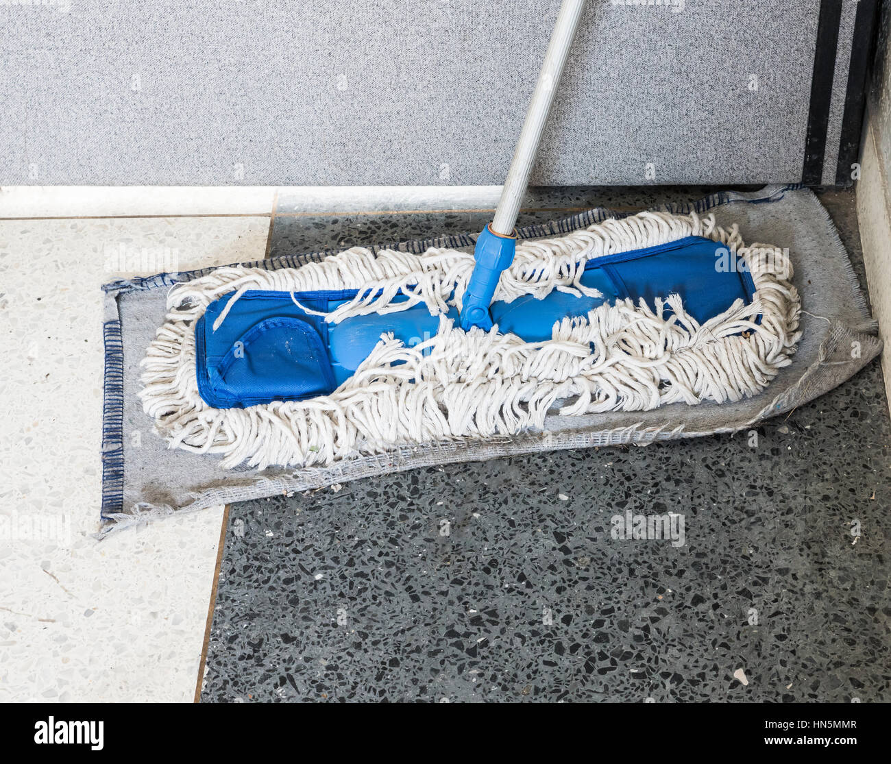 Dirty old mop with the dust on the office floor. - Stock Image