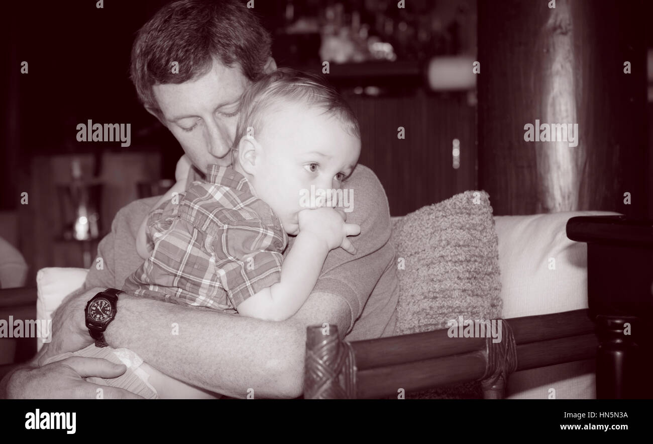 Father Holds Boy Toddler & Gives him Comfort Inside a Restaurant on Mexico - Stock Image