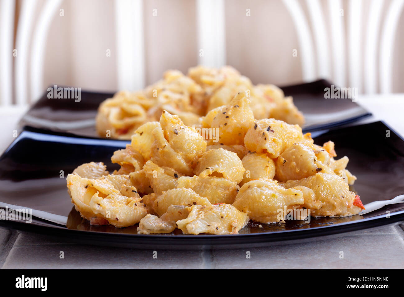 pasta on a dark plate on the table - Stock Image