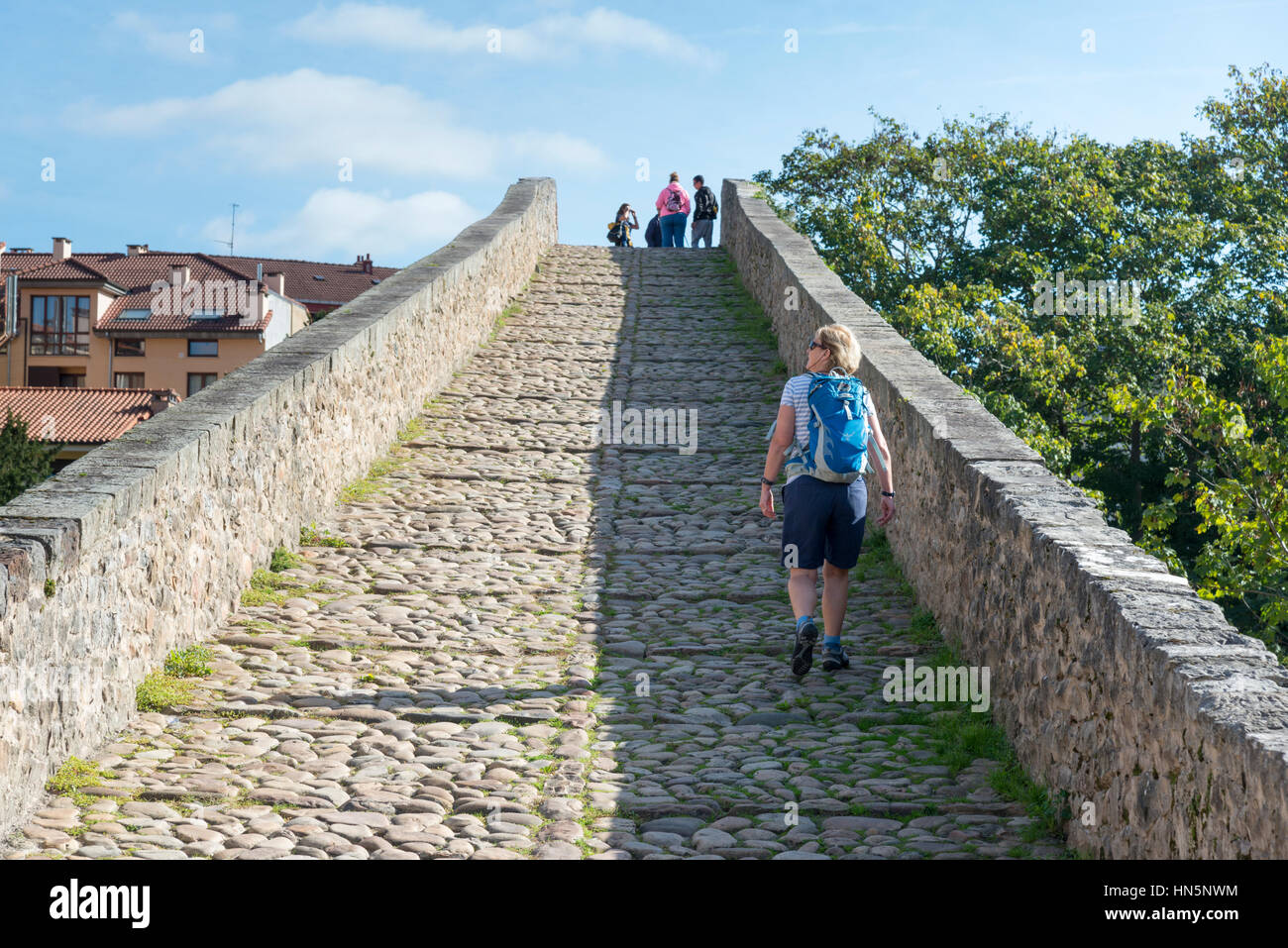 A woman tourist walks over the Roman Bridge of Cangas de Onis an ancient stone bridge over the river Sella in the Stock Photo