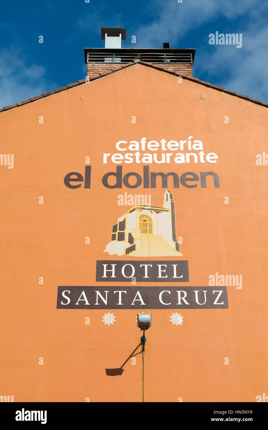 A mural advert or advertisement on the side of a wall of a building in Spain for the Cafe Dolmen and Hotel Santa - Stock Image