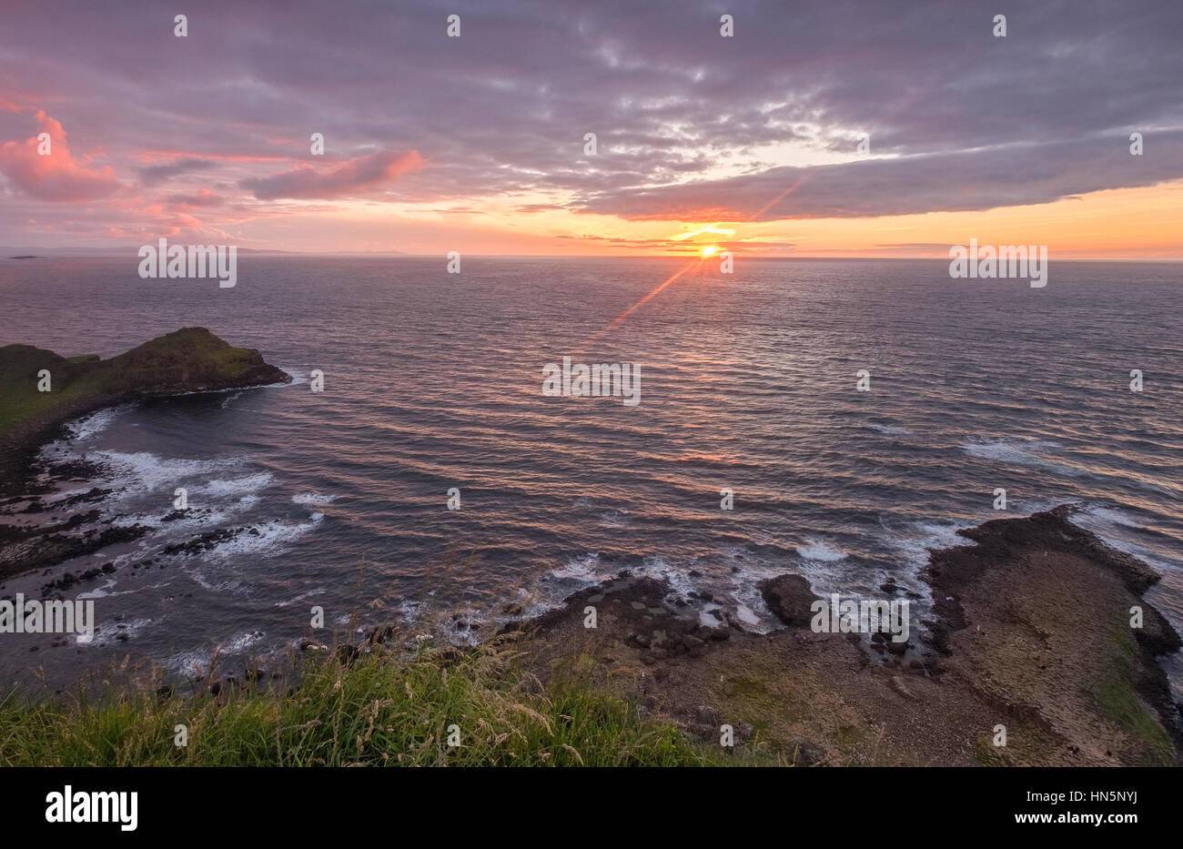 High above the famous stones at The Giants Causeway in Northern Ireland as the sun sets on the horizon - Stock Image