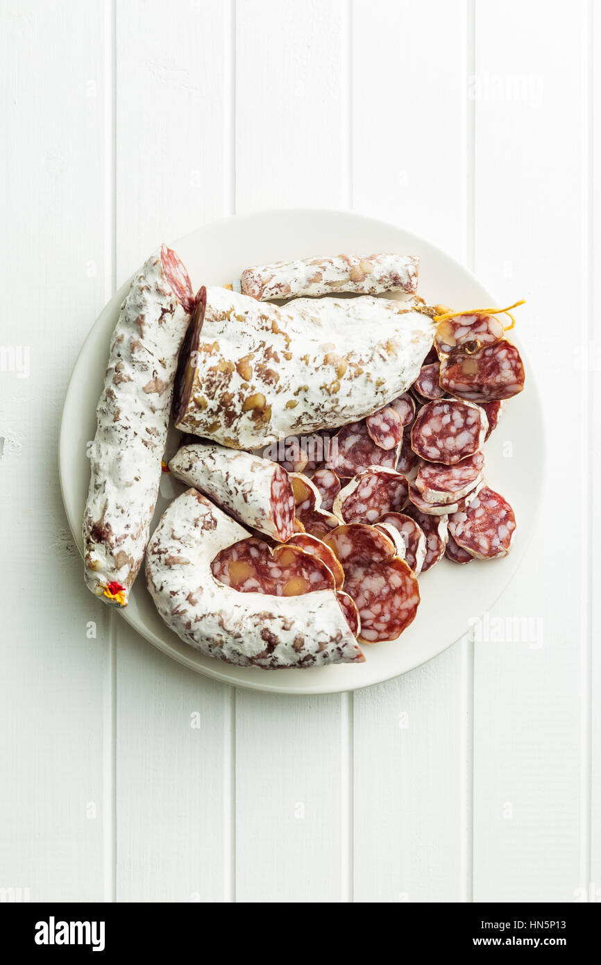 Tasty sliced salami with white mold. - Stock Image