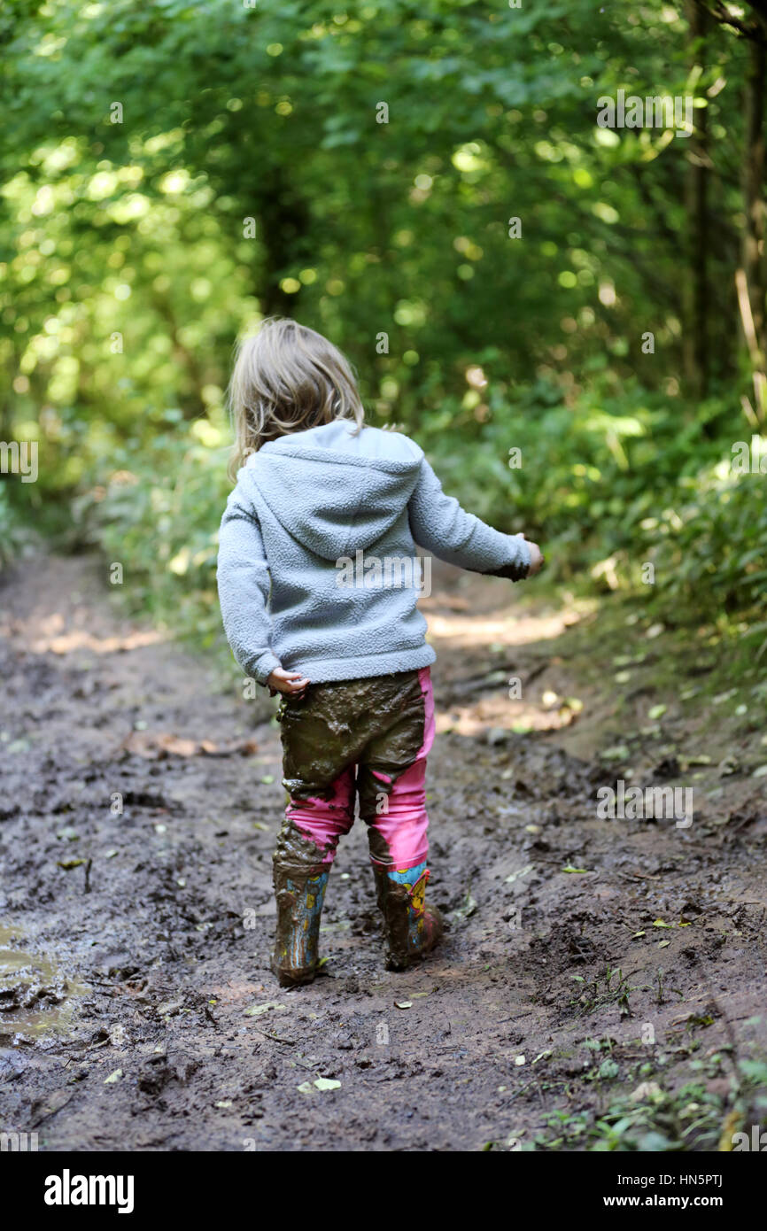 A young child hols the back of her trousers away from her body after falling on her backside in wet mud - Stock Image