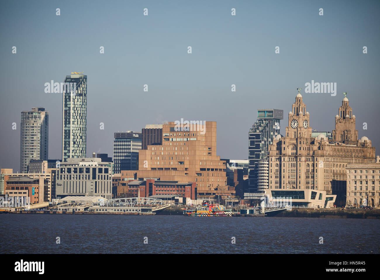 From Birkenhead side of the River Mersey looking out over Liverpool city centre on a blue sky day at landmark waterfront - Stock Image