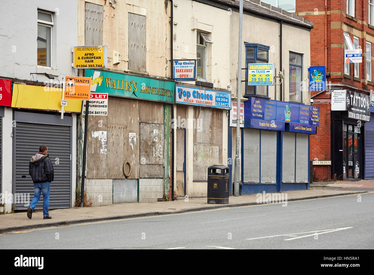 A closed rundown and boarded up windows of independent retail shops on a terraced street in Bolton Town Centre, - Stock Image