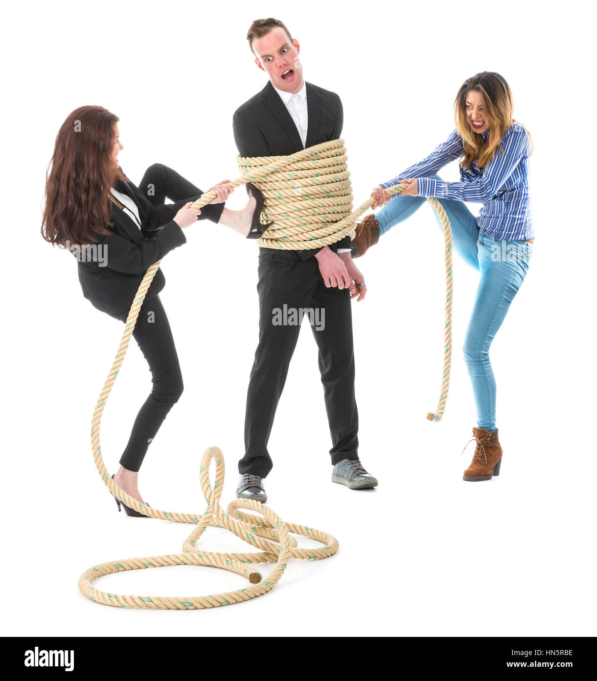 Two angry woman tying a business man with rope, isolated on a white background - Stock Image