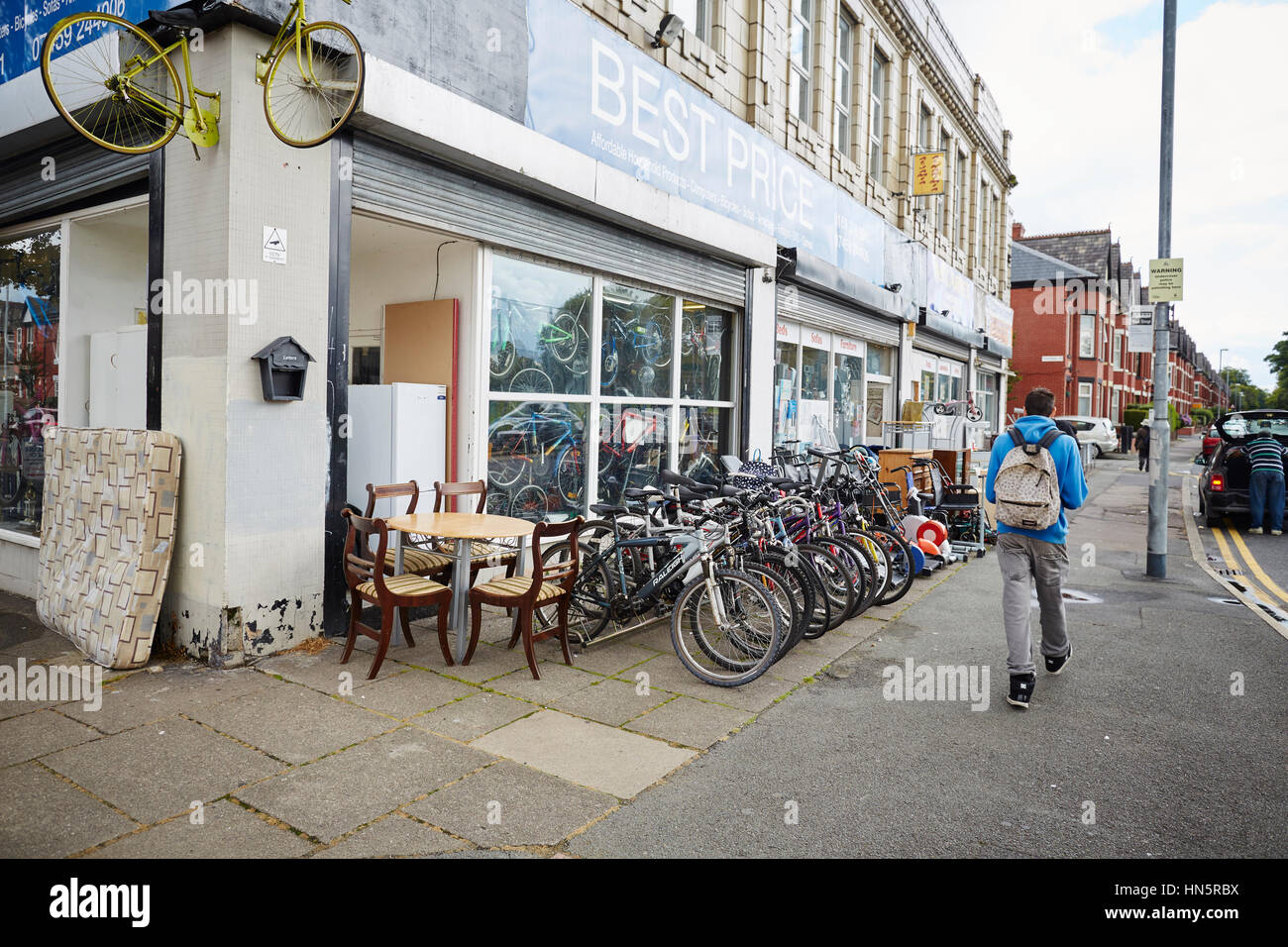 Exterior of Best Price a secondhand junk shop with bicycles and furniture on display on the pavement on Platt Lane, - Stock Image
