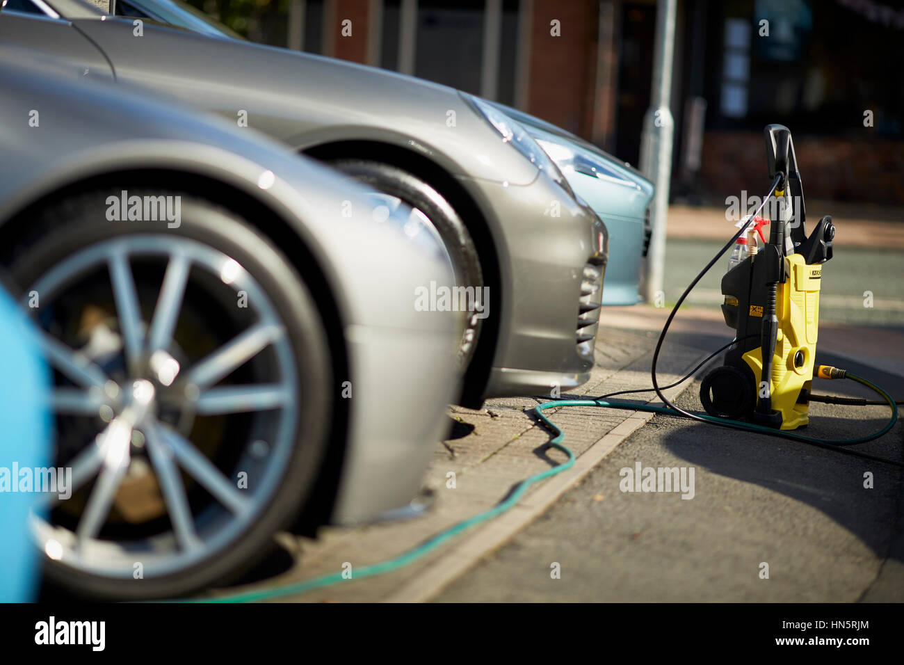 Sunny day in wealthy Cheshire village Wilmslow luxury secondhand car lot sales pitch & showroom for Aston Martin - Stock Image