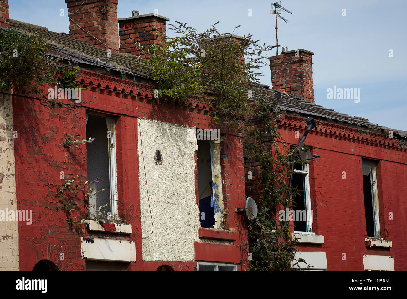fenced off warning keep out sign derelict condemned empty houses, typical brick built 2 up 2 down terraced street - Stock Image