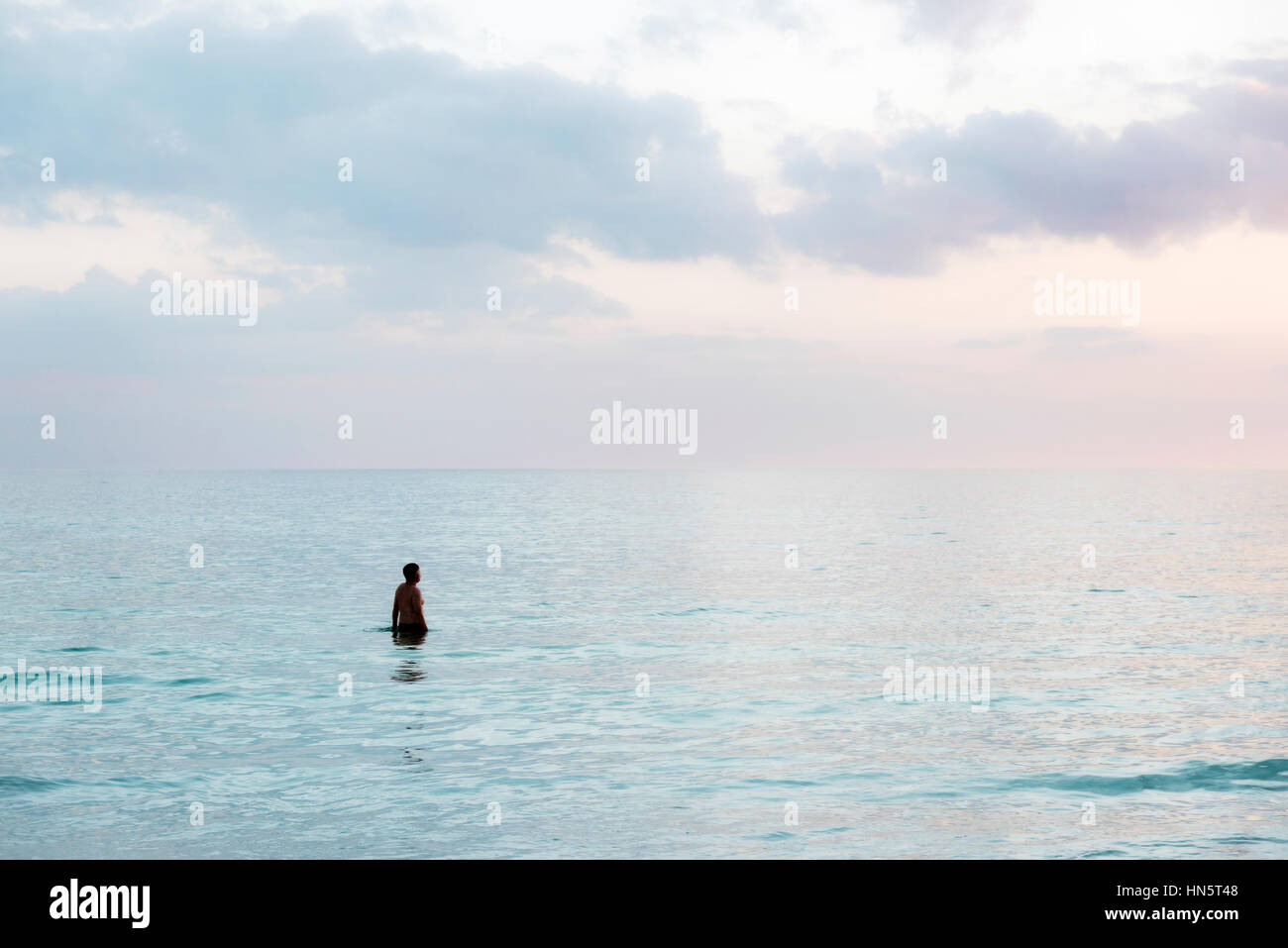 Solitary man in tropical ocean water, Siesta Key Beach, Florida, USA. - Stock Image