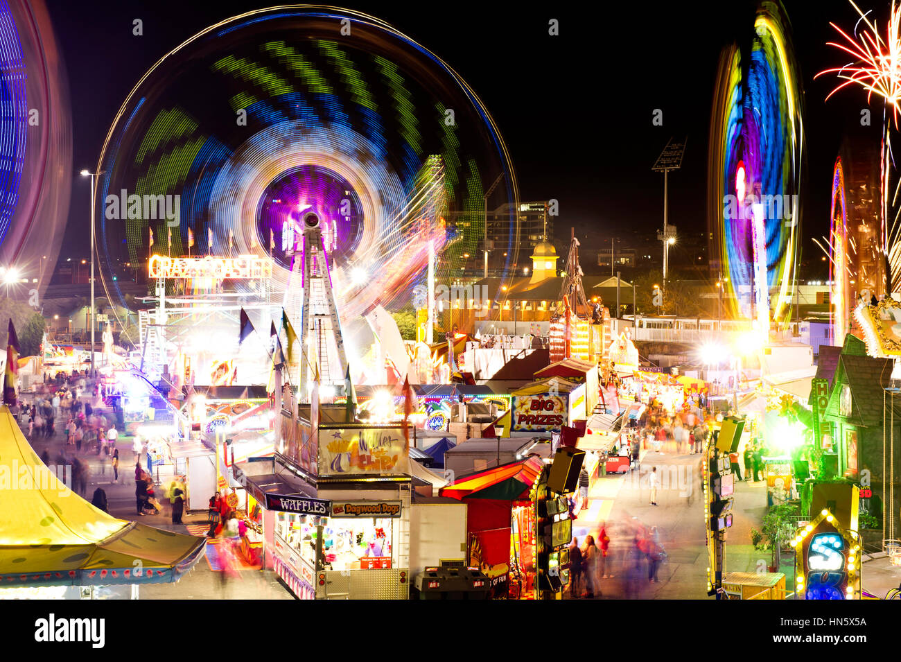 Fairground carnival rides at night time - Stock Image