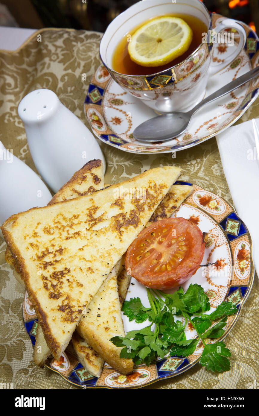 An English breakfast dish of Gypsy Toast served with grilled Tomato, garnished with fresh Parsley. Stock Photo
