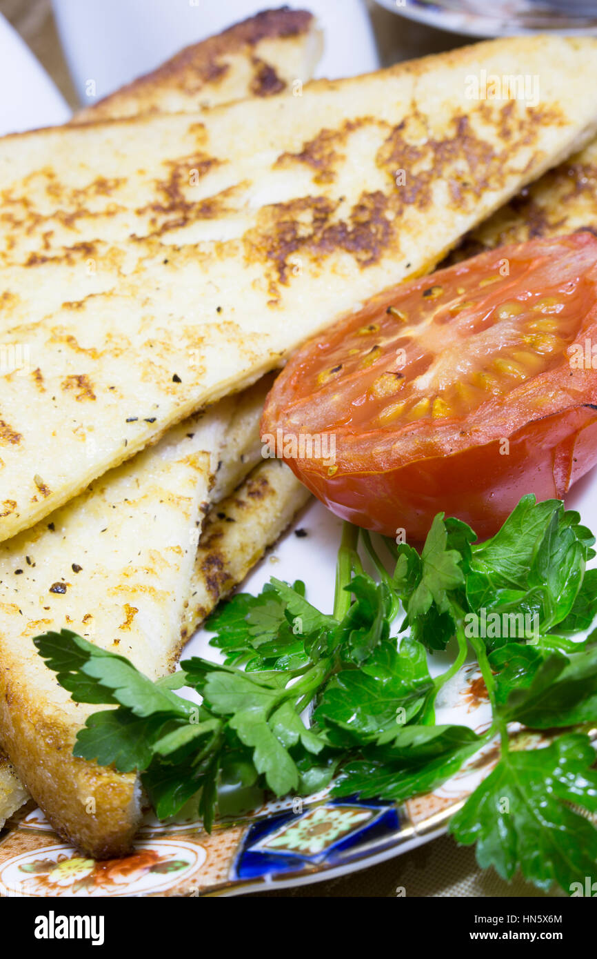 Close up of a portion of Gypsy Toast served with grilled Tomato and Parley garnish. Stock Photo