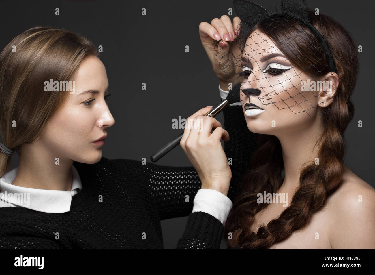 Two beautiful girls on photo shoot to apply face makeup . Beauty fashion model. - Stock Image