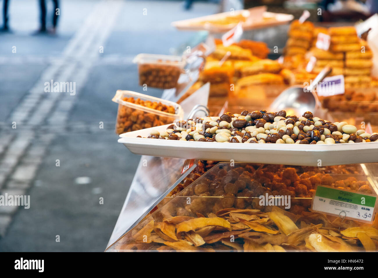 Chocolate macadamia nuts on display at a dried fruits and nuts stall in Borough Market, London - Stock Image