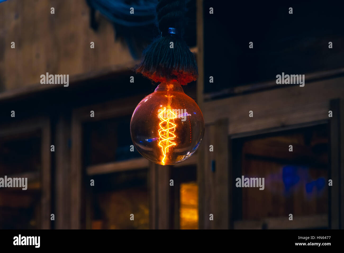 Hanging decorative filament light bulb in a dim atmosphere - Stock Image