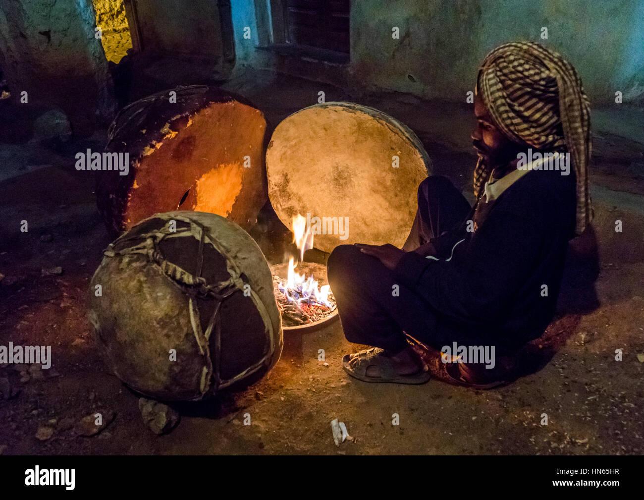 Harari man heating the drums before a ceremony in sufi community, Harari Region, Harar, Ethiopia Stock Photo