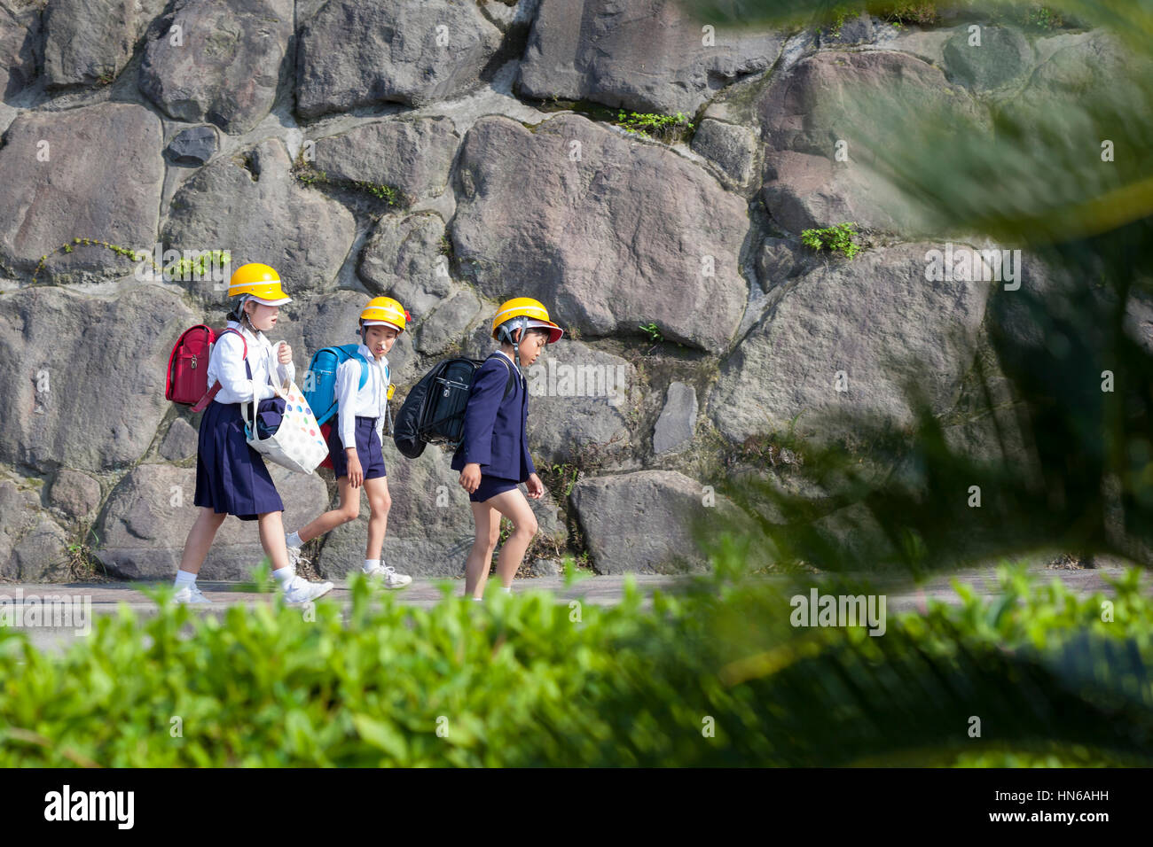Sakura-jima, Japan - April 23, 2012: Three schoolchildren walk home wearing hard hats to protect against potentially - Stock Image