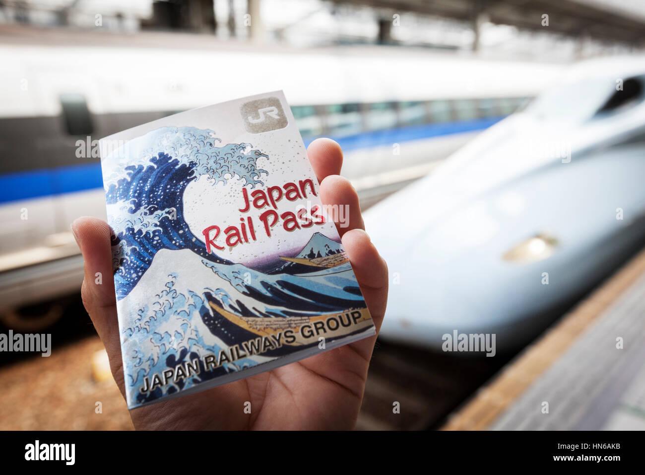 Okayama, Japan - May 8, 2012: Close-up of a male hand holding a Japan Rail Pass at Okayama train station with Shinkansen - Stock Image
