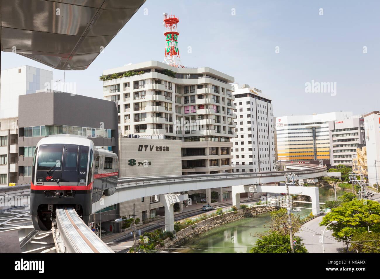 NAHA, JAPAN - APRIL 1: A train snakes past modern buildings on the Okinawa City Monorail line in Naha, Okinawa Island, - Stock Image