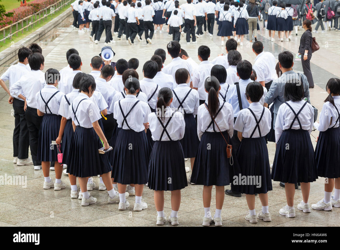 Nara, Japan - May 9, 2012: A large group of Japanese school children in uniforms and a guide with a loud hailer - Stock Image