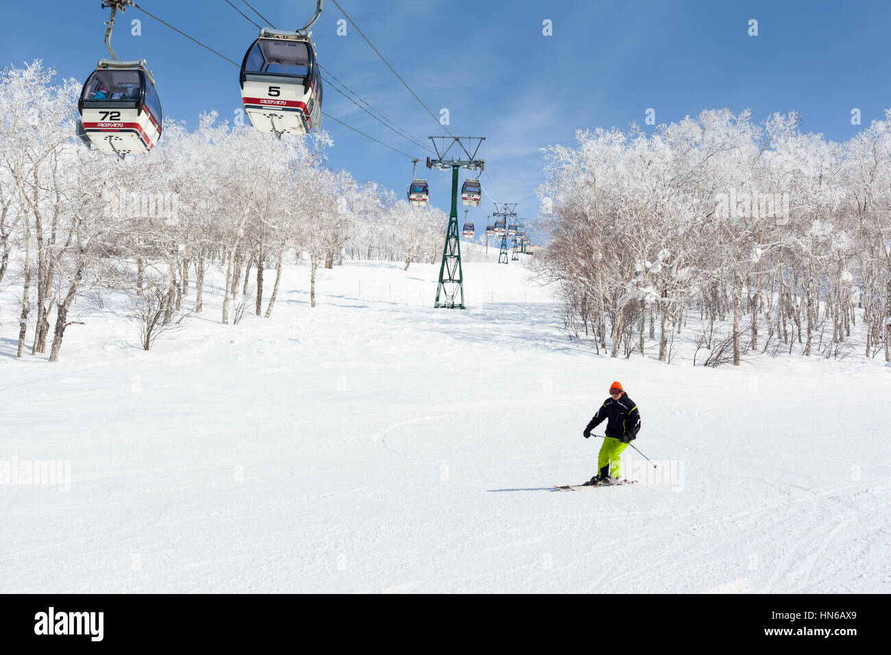 NISEKO, JAPAN - MARCH 9 : A man skis past a gondola lift in the Niseko Annupuri ski resort on 9th March 2012. Niseko - Stock Image