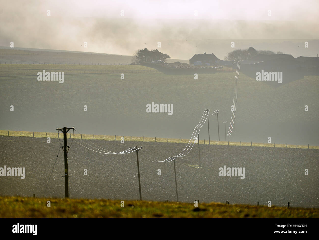 Power lines linking a small remote farm to the national grid, South Downs National park in East Ssussex - Stock Image