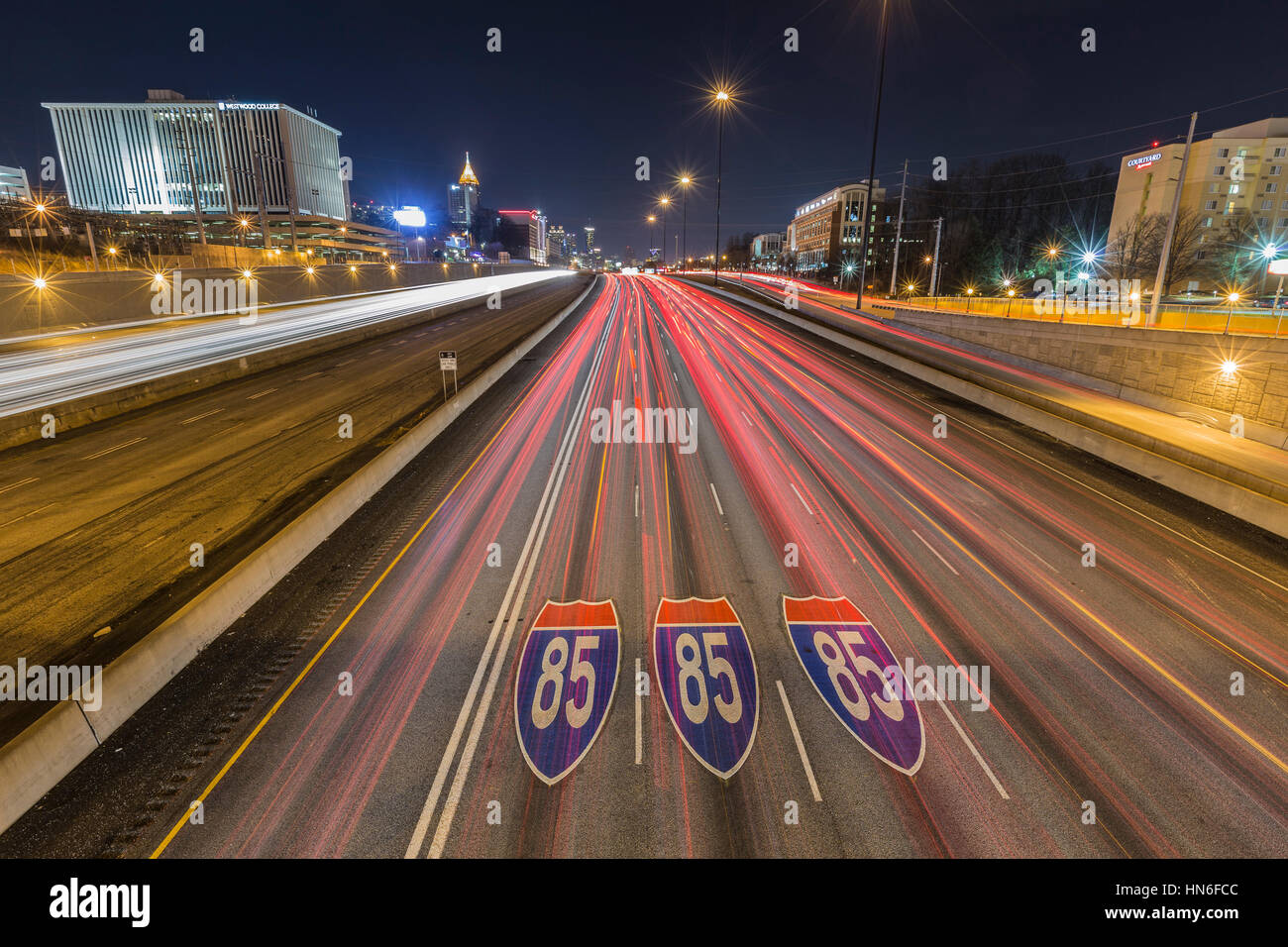 Atlanta, Georgia, USA - February 15, 2014:  Interstate highway 85 pavement signs, downtown skyline and traffic at Stock Photo