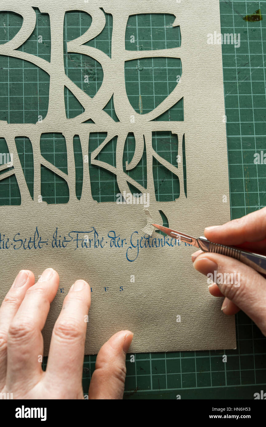 Calligraphy studio, hand holding scalpel with paper cutting, sheet with text from paper cutting, Seebruck, Upper Stock Photo