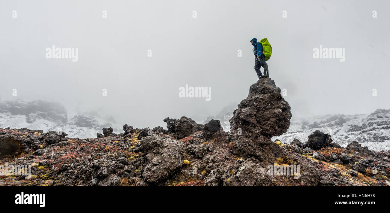 Hiker standing on rock, Tongariro Alpine Crossing with snow, Tongariro National Park, Southland, New Zealand - Stock Image